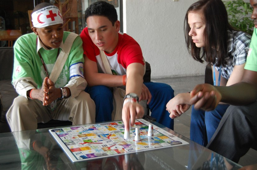 Youths playing a climate change awareness/education game (based around the Snakes & Ladders game) developed by the Colombian Red Cross.