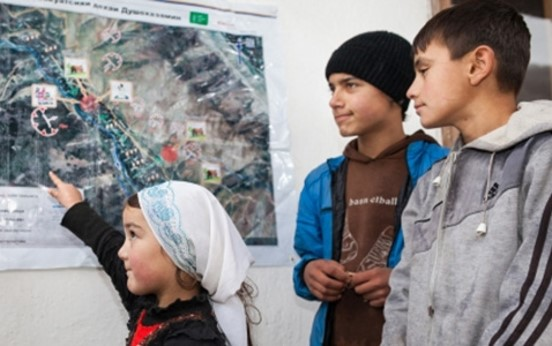 This is an image from a Mercy Corps school safety program in Tajikistan showing a young girl highlighting on a map areas of risk in her community.